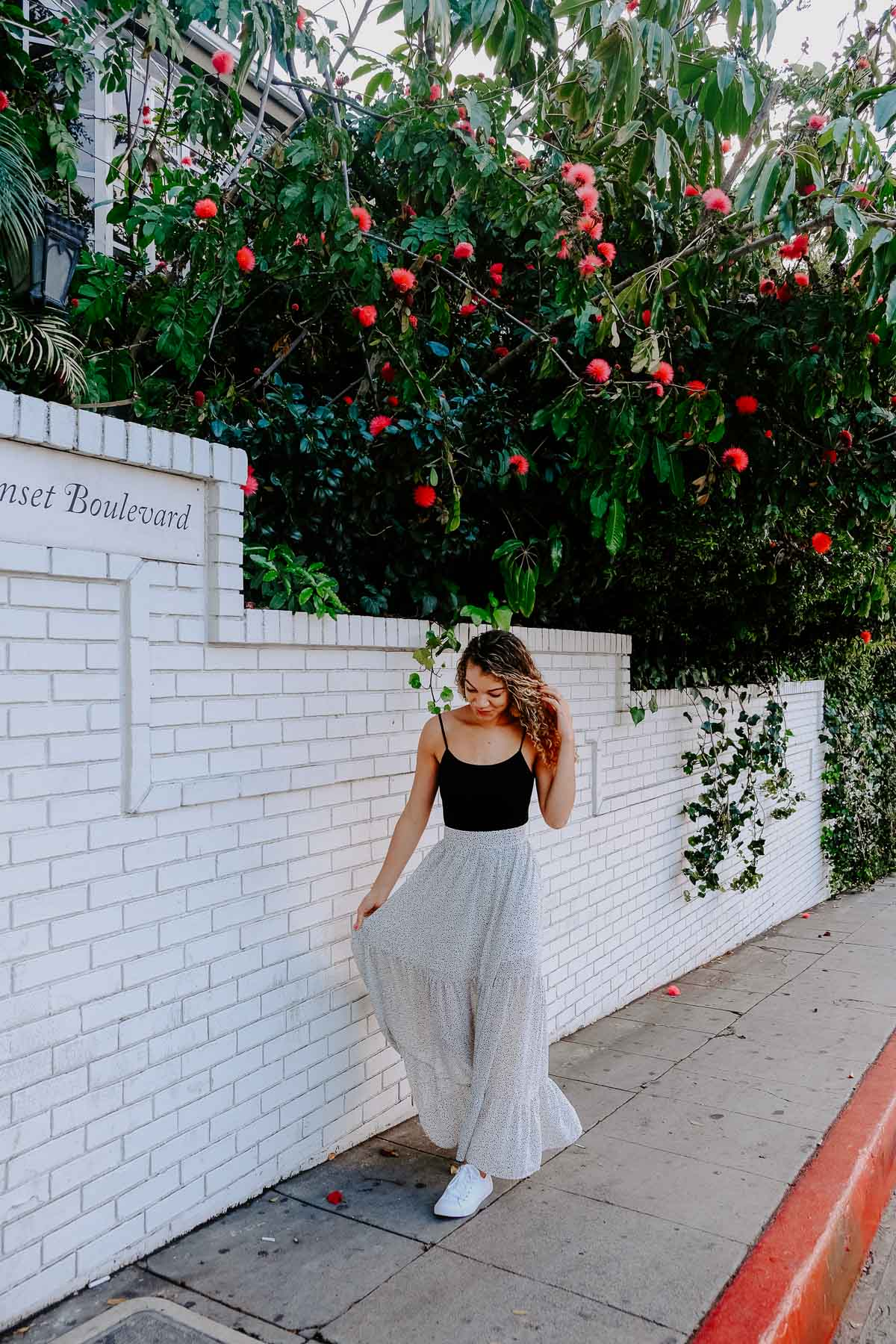 Planning a trip to LA and need to know what to wear? This post has the LA packing essentials that you need for a trip to Los Angeles! This maxi skirt and white sneaker outfit would be perfect to add to your summer outfits!