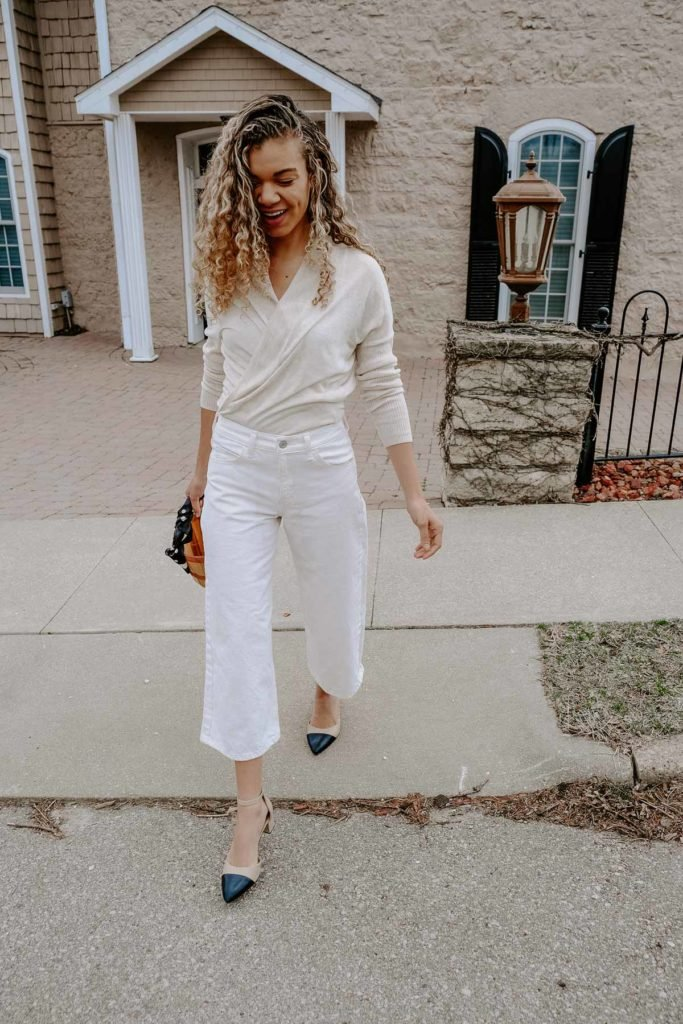 white cropped flare jeans and a beige top
