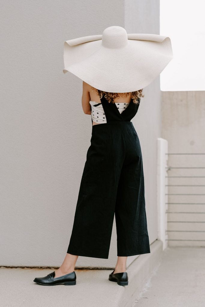 black linen jumpsuit with a straw hat