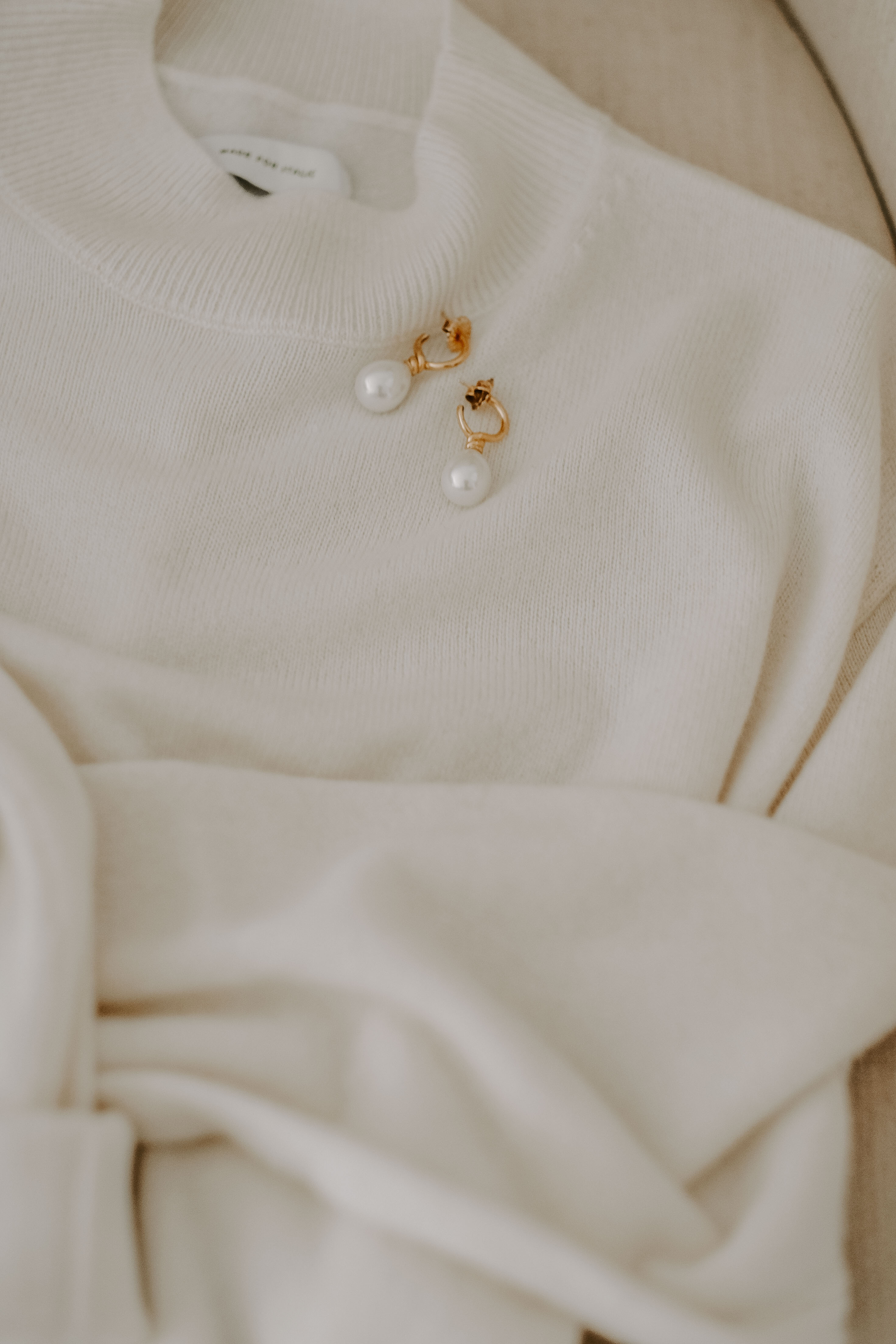 cashmere sweater and pearl earrings