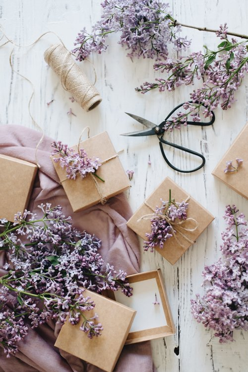 Gifts flatlay with lilac flowers