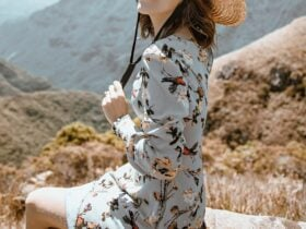 Young white Woman wearing blue floral dress in field on a sunny day