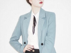 White woman wearing a light blue blazer and black jeans