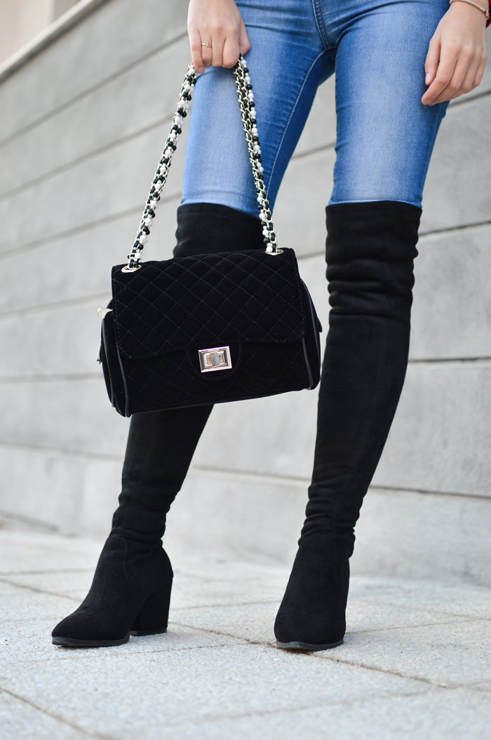 white woman wearing black over the knee boots and skinny jeans