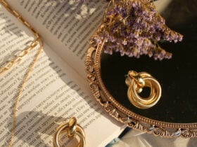 small golden hoop earrings laying on a mirror and open book