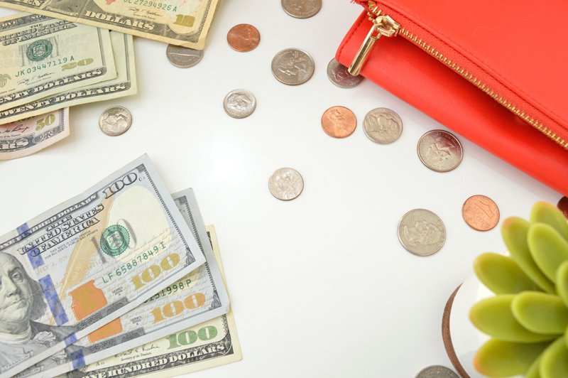 Flatlay of $100 notes and a red purse