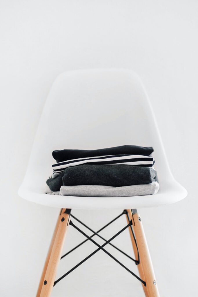 White Eiffel chair stacked with clothes