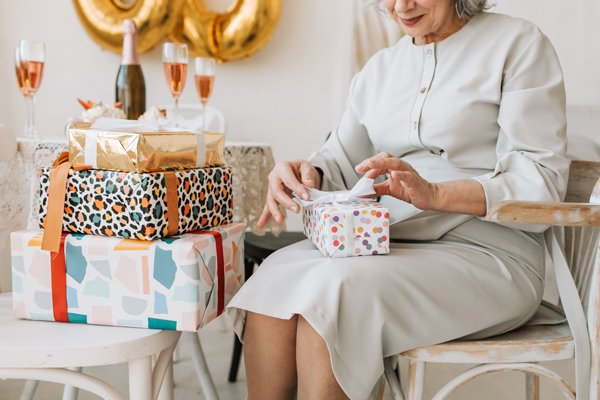 Elderly woman unwrapping birthday gifts