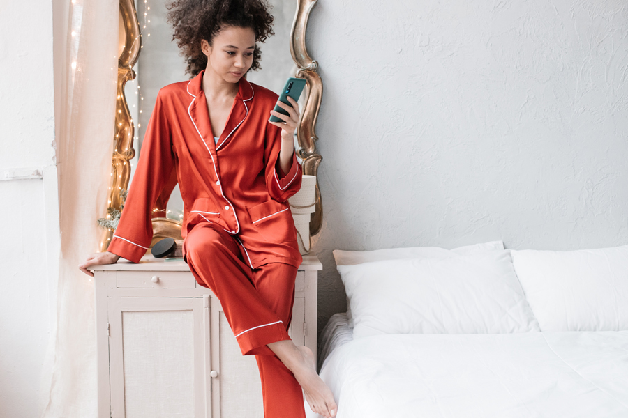 Biracial woman wearing red silk pajamas in a bedroom while holding her phone