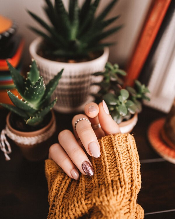 White woman wearing an orange sweater with a silver and nude manicure