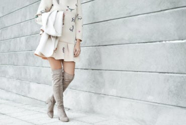 White woman wearing gray kne-high boots and white short dress