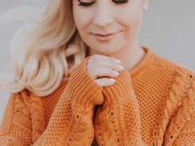 Blonde woman wearing an orange autumn sweater